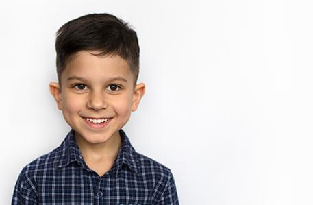 Latin American Boy Smiling Against White Background