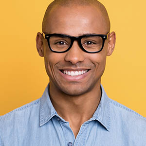 man with glasses smiling after cosmetic dentistry services in jersey village