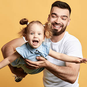 man holding up daughter like an airplane carefree from dental insurance payments