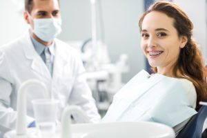 young woman smiling in specialty dentist chair with dental braces in tx