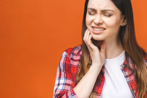 woman struggles with the pain associated with impacted teeth