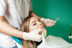 Doctor performs a tooth extraction on a female patient